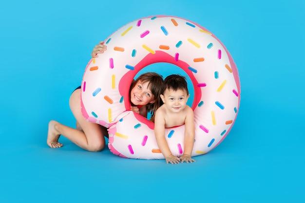 Neonato felice e sorella maggiore in costume da bagno con la ciambella dell'anello di nuoto su una parete blu colorata
