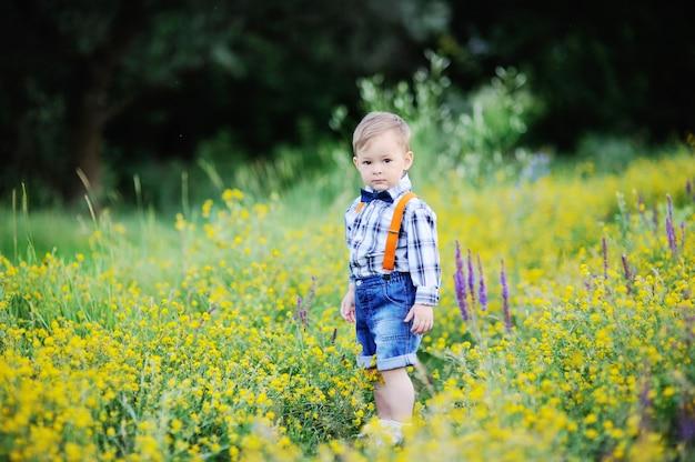 Neonato in bretelle arancioni e farfallino su un campo di sfondo di fiori
