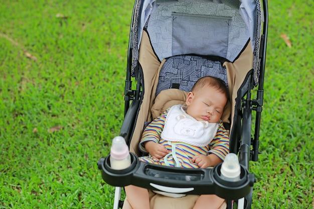 Neonato neonato asiatico del primo piano che dorme in passeggiatore sul parco naturale.