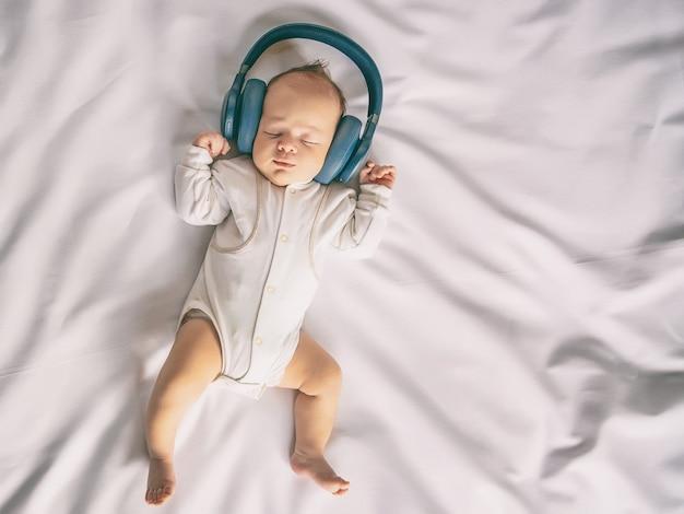 Neonato sorridente che ascolta la musica con le cuffie e sdraiato sul foglio bianco nella culla, felice infanzia spensierata del bambino, tonica immagine, vista dall'alto