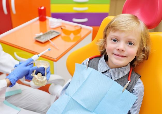 Neonato sorridente con capelli ricci biondi in sedia dentale.