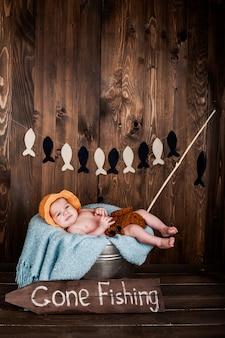 Neonato, studio fotografico su uno sfondo di legno