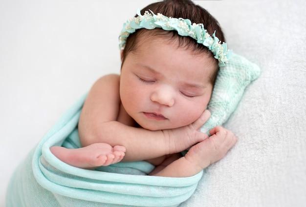 Neonato sveglio che dorme sul cuscino minuscolo