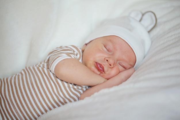 Neonato sveglio del piccolo bambino che dorme a casa