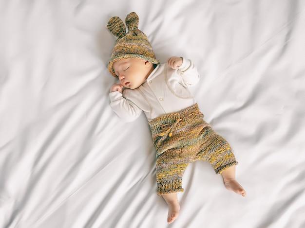 Neonato sveglio in cappello divertente con le orecchie del coniglietto sta dormendo dolcemente nella culla sul foglio morbido bianco, primo piano, vista dall'alto