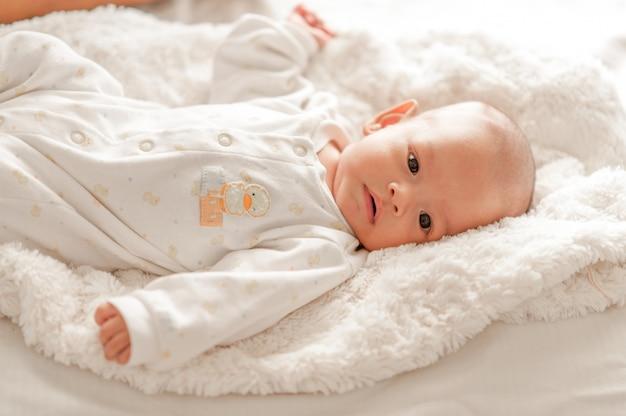 Neonato sveglio in una camera da letto di luce bianca il bambino appena nato è carino. in biancheria da letto per bambini nati - immagini