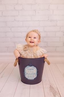 Neonato sveglio nella borsa del secchio della decorazione creativa. ragazza infantile che si siede all'interno della ciotola. colori mignolo