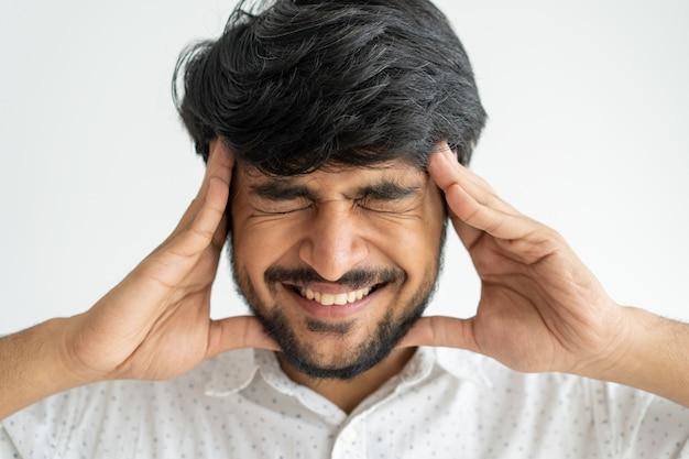 Nervoso uomo indiano emotivo toccando la testa con le mani mentre si sente emicrania.