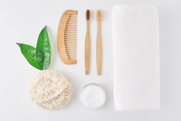 Nessun concetto di plastica a zero rifiuti. spazzolini da denti, asciugamano, polvere di dente, pettine e pezzuola per lavare di bambù di legno amichevoli di eco su un fondo bianco, vista piana di vista superiore
