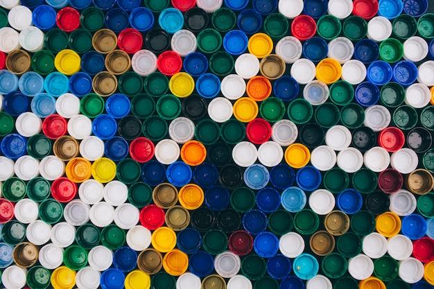 Nessun concetto di plastica. concetto di problema di inquinamento. sfondo colorato di diversi coperchi di plastica. di 'no alla plastica monouso. rifiuta il concetto di plastica monouso
