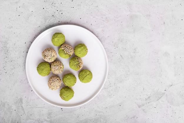 Nessun morso di energia matcha o palline, preparati con ingredienti naturali, come noci, polvere di matcha, datteri. vista dall'alto