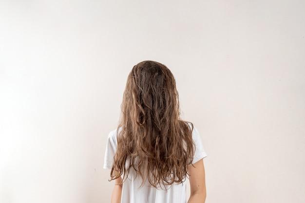 Nessun volto ritratto di giovane donna con i capelli castani e disordinati. concetto assonnato