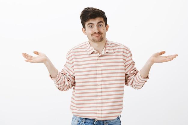 Nessuna idea. modello maschio caucasico indifferente all'oscuro con baffi, palme aperte e scrollata di spalle, inconsapevole e confuso, sorridente goffamente