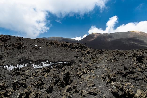 Neve sotto la cenere vulcanica sulla cima del vulcano etna in sicilia, italia