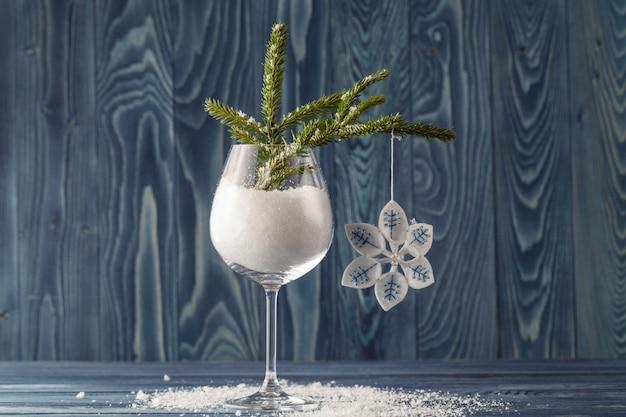 Nevichi in vetro di vino, rami di albero e palle di natale su vecchio fondo di legno, fuoco selettivo