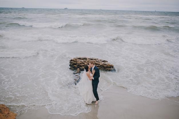 Newlyweds che baciano sulla spiaggia
