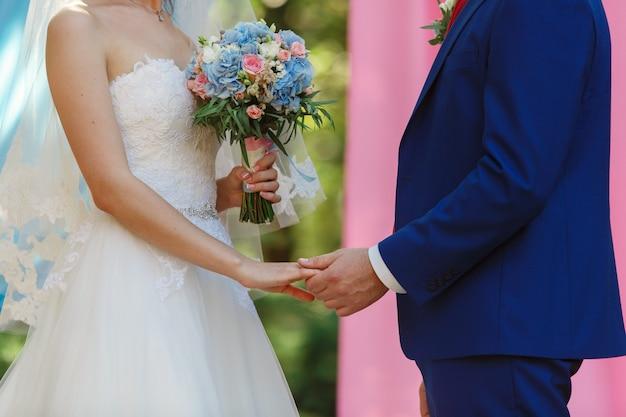 Newlyweds che si tengono per mano al giorno delle nozze soleggiato. sposa con un bel mazzo di fiori rosa e bianchi e lo sposo in abito blu. cerimonia di matrimonio all'aperto. matrimonio. momento romantico da vicino