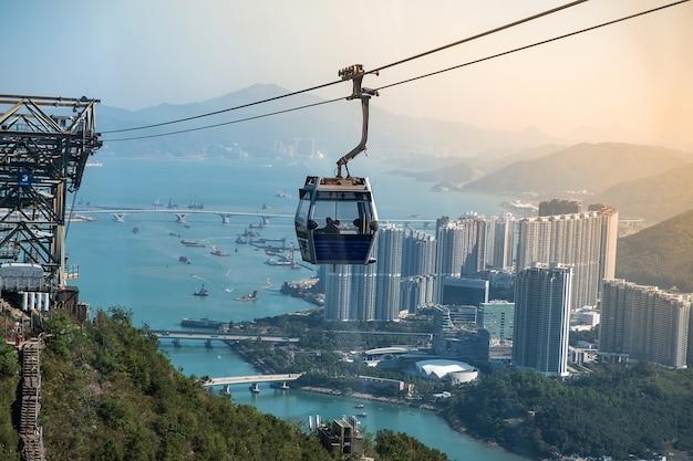 Ngong ping cable car con i turisti sopra il porto, le montagne e il fondo della città a hong kong