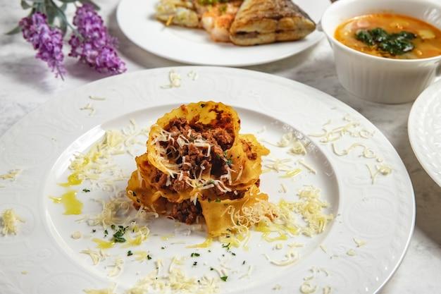 Nido della tagliatella con la vista laterale delle spezie del burro di verdi di formaggio tritato della carne