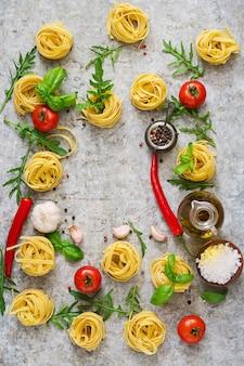 Nido di tagliatelle di pasta e ingredienti per cucinare (pomodori, aglio, basilico, peperoncino). vista dall'alto
