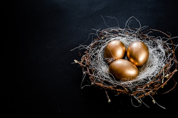 Nido di uova di pasqua d'oro su sfondo nero. vacanze di pasqua