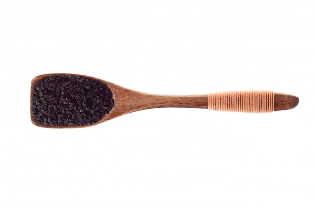 Nigella della spezia o semi di cumino neri in cucchiaio di legno isolato su un fondo bianco, vista superiore