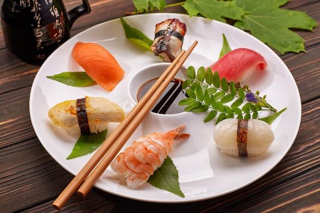 Nigiri sushi con tonno, salmone, gamberi, capesante, anguilla, frittata, su un piatto bianco con salsa di soia