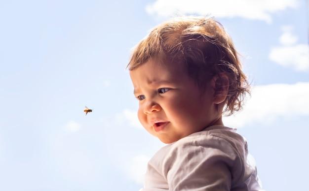 Niña de 15 meses observa una abeja mientras vuela