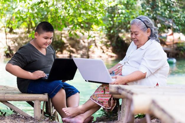 Nipote che insegna al suo computer portatile femminile anziano di uso