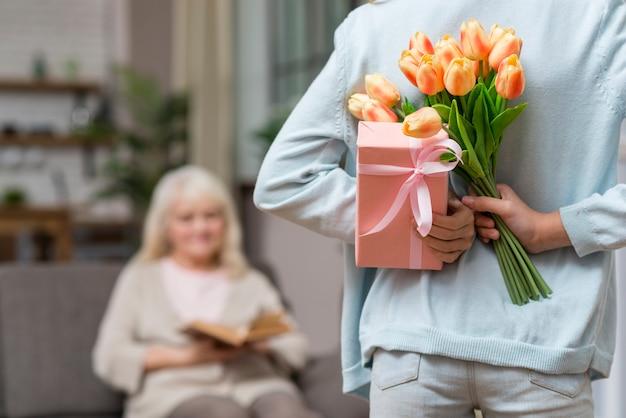 Nipote che nasconde un regalo a sua nonna