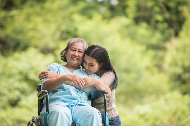 Nipote che parla con sua nonna che si siede sulla sedia a rotelle, concetto allegro, famiglia felice