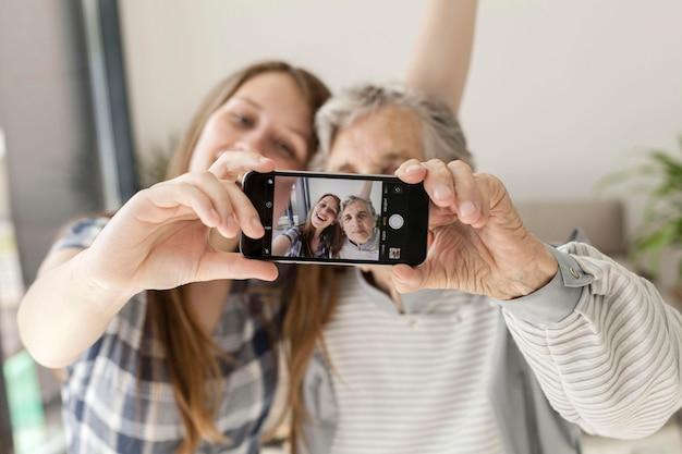 Nipote che prende selfie con la nonna