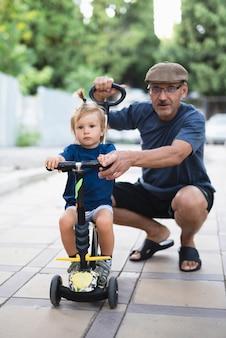 Nipote con nonno in sella a una bicicletta