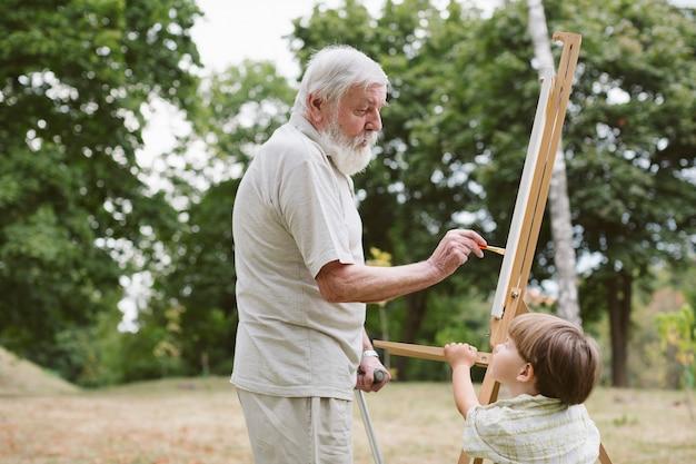 Nipote di vista frontale che esamina la pittura del nonno