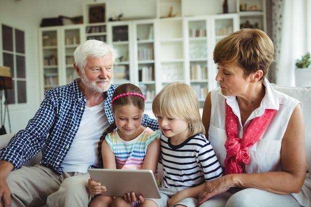 Nipoti che utilizzano la tavoletta digitale con i nonni