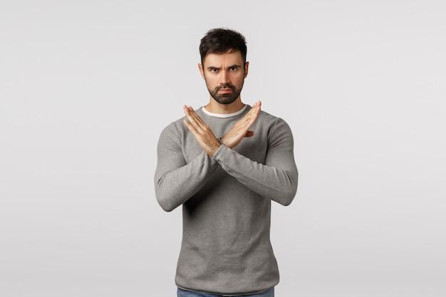 No, non accettarlo mai. uomo barbuto serio e fiducioso in maglione grigio, facendo un gesto di arresto incrociato, limitando il partner a fare cattive azioni, dare una risposta negativa, rifiutare o vietare