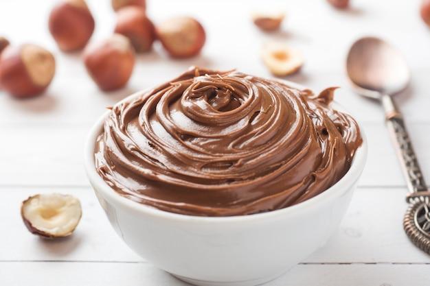 Nocciola noce cioccolato in un piatto su uno sfondo bianco con nocciole. concetto di colazione.