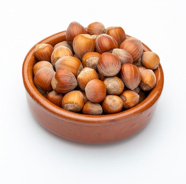 Nocciole in coppa di argilla (raccolta varie noci). isolato