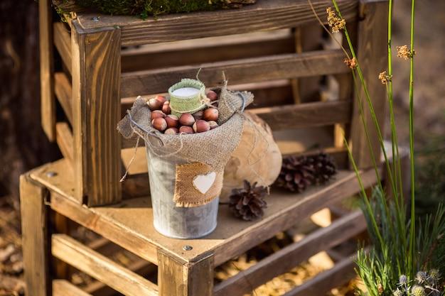 Nocciole in secchio con cuore bianco su scatole di legno. decorazioni in stile rustico