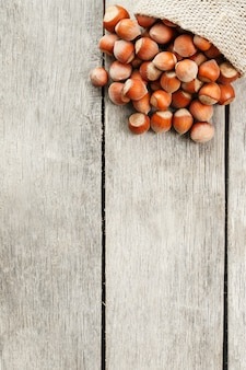 Nocciole in una copertina, versato da una borsa di tela da imballaggio su un tavolo di legno grigio