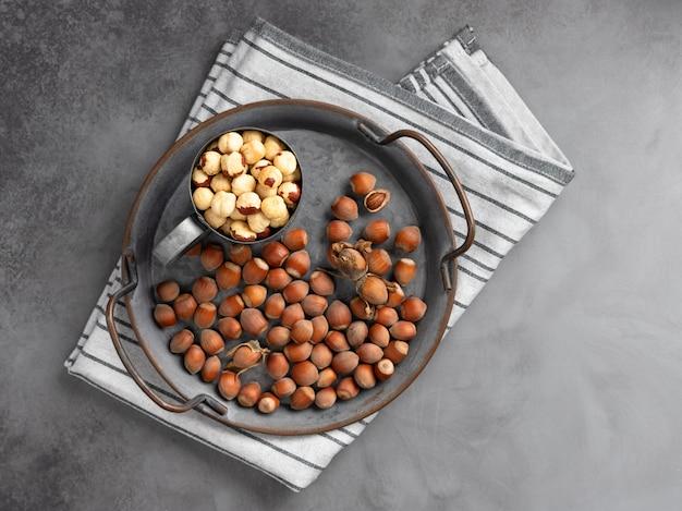 Nocciole sbucciate in una tazza su una nocciola intera. cibo salutare