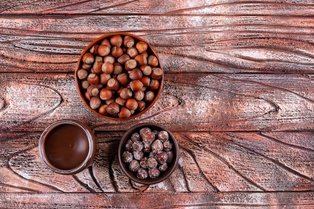 Nocciole sgusciate e spalmate in una vista superiore della ciotola marrone su una tavola di legno