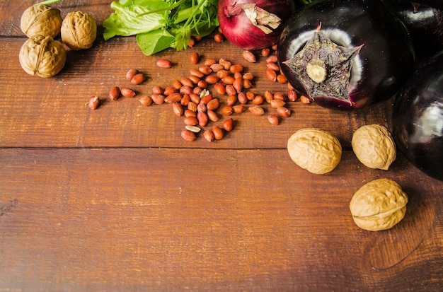 Noce; arachidi e verdure su fondo strutturato in legno marrone