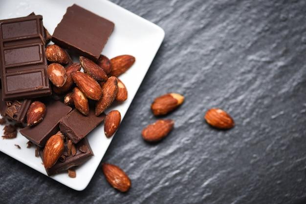 Noce delle mandorle del cioccolato sul piatto bianco sui precedenti scuri