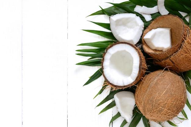Noce di cocco. cocco intero, coperture e foglie verdi su una tavola di legno bianca. grande dado. cocco della frutta tropicale nelle coperture. spa. foto di cibo. foto di sfondo. trama di frutta tropicale. copia spazio