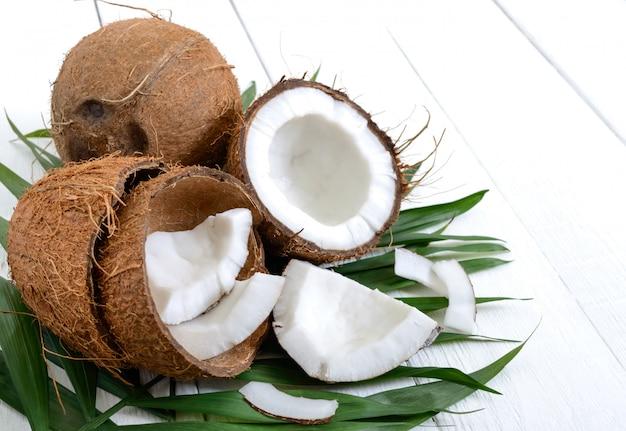 Noce di cocco. cocco intero, coperture e foglie verdi su una tavola di legno bianca.