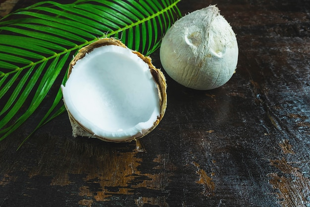 Noce di cocco con foglie su fondo in legno