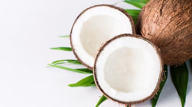Noce di cocco con foglie verdi su sfondo bianco.
