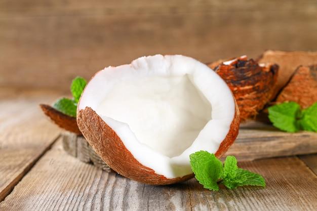 Noce di cocco con la menta sulla vecchia tavola di legno