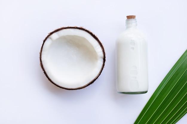 Noce di cocco con latte di cocco su sfondo bianco.